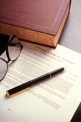 Book, pen and Power of Attorney document on a desktop